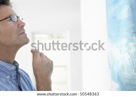 Man observing painting in art gallery - stock photo