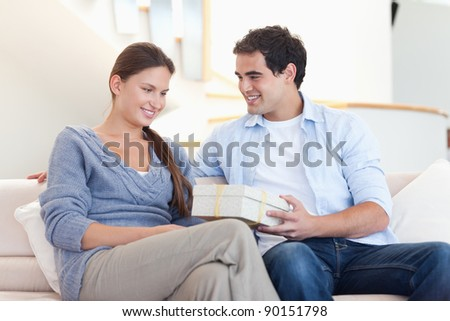 Man offering a gift to his girlfriend in their living room