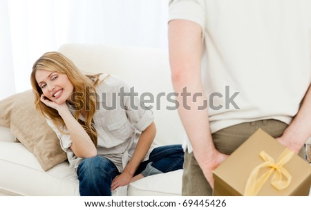 Man offering a gift to his wife - stock photo