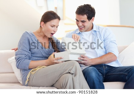 Man offering a present to his wife in their living room - stock photo