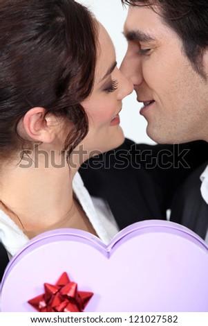 Man offering girlfriend heart-shaped box of chocolates - stock photo