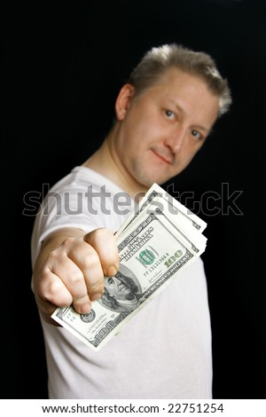 Man offering money over black background. Focus on the money! - stock photo