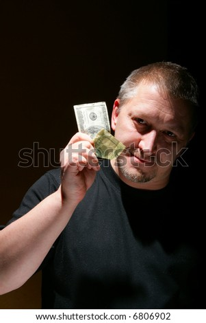 Man offering money over black background with space for your own text above and  below. - stock photo