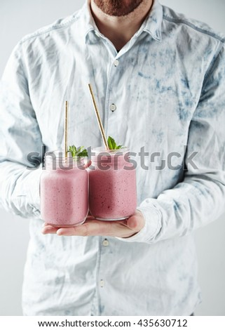Man offers on camera two rustic jars with tasty cold berry smoothies Healthy refreshment beverage for summer time with drinking straw inside - stock photo