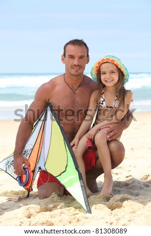 Man on a beach with his daughter and a kite - stock photo