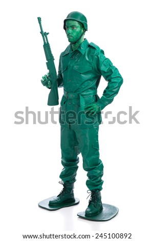 Man on a green toy soldier costume standing with riffle isolated on white background. - stock photo