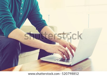 Man on a laptop in bright window lit room