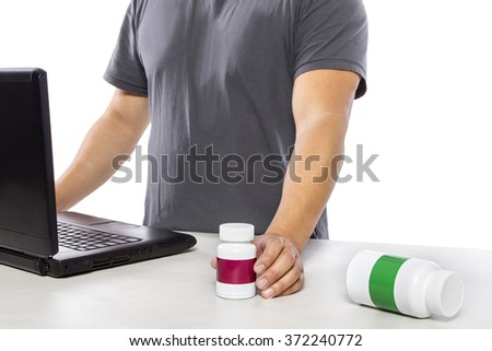 Man on a laptop ordering or researching competing brands of supplements online.  He is buying from an online pharmacy or comparing medicine and generic drugs. - stock photo
