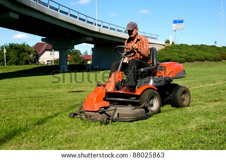 Man on a riding lawn mower - stock photo