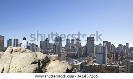 Man on a rock watching the city of Montreal - stock photo