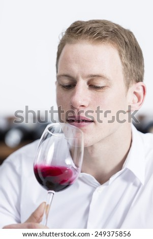 man on a wine tasting session on the olfactory phase is analyzing the red wine shaking the glass of wine at a restaurant - focus on the man face - stock photo