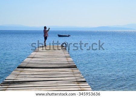 Man on an old wooden pier takes photo of the sea
