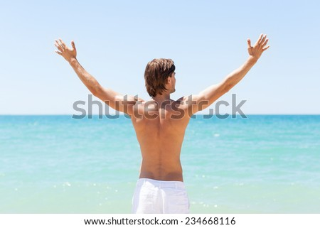 man on beach hold hands arms up, rear view guy summer, standing back looking to sea blue sky horizon, vacation concept of freedom travel ocean - stock photo