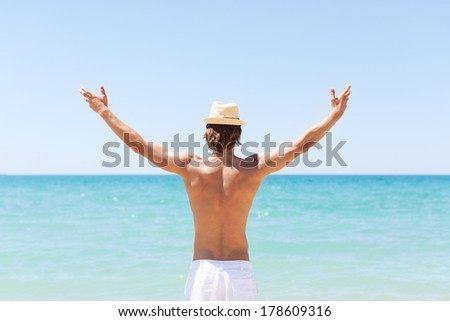 man on beach hold hands arms up, rear view guy wearing summer hat, standing back looking to sea blue sky horizon, vacation concept of freedom travel ocean