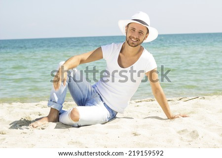 Man on beach lying in sand looking to side smiling happy wearing hipster summer hat. Young male model enjoying summer travel holiday by the ocean. - stock photo