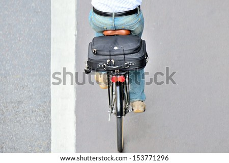 Man on bicycle on his way home from work, in bike lane - stock photo