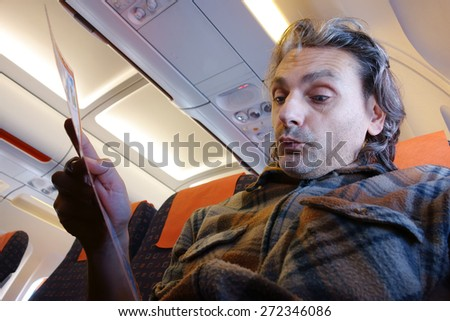man on board reading Flight Rules and Safety Precautions - stock photo