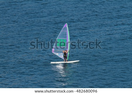Man on board with sail for surfing