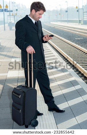 man on business trip using his smartphone - stock photo