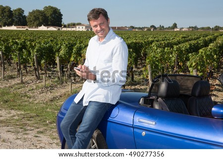 Man on cabriolet with cell phone