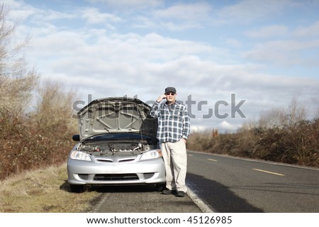 Man on cellphone with car trouble. - stock photo