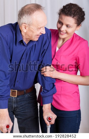 Man on crutches and his nurse, vertical - stock photo