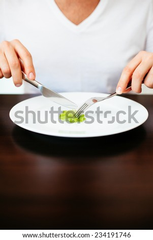 Man on diet cutting a tiny piece of lettuce on a white plate - stock photo