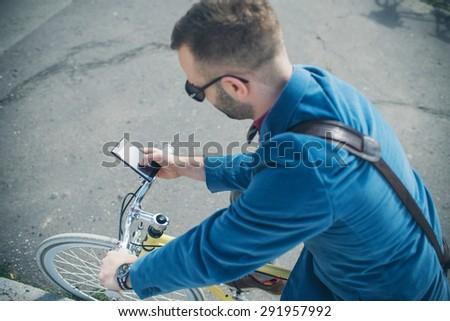 Man on his bike using smartphone - stock photo