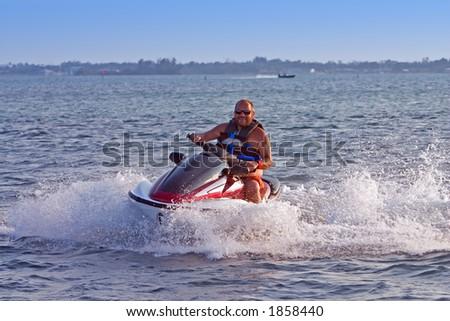 Man on jet ski in motion - stock photo