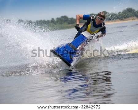 Man on jet ski in the river skims along camera - stock photo
