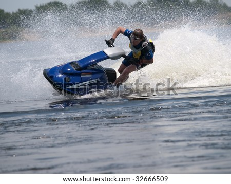 Man on jet ski in the river turns with much splashes - stock photo