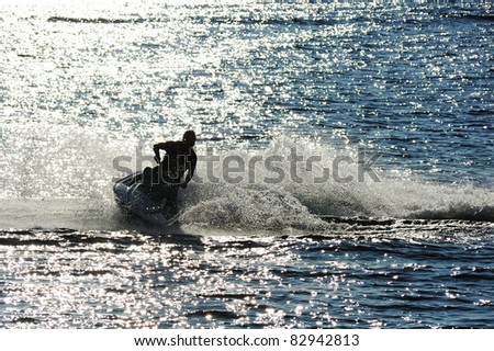 Man on Jet Ski turns fast on the water - stock photo