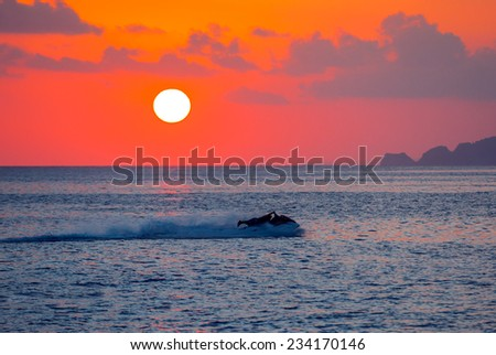 man on jetski at sunset - stock photo