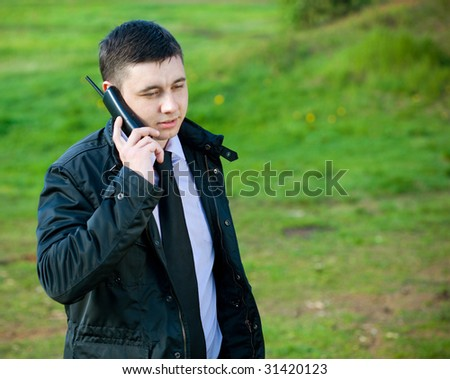 man on mobile phone on natural green background - stock photo