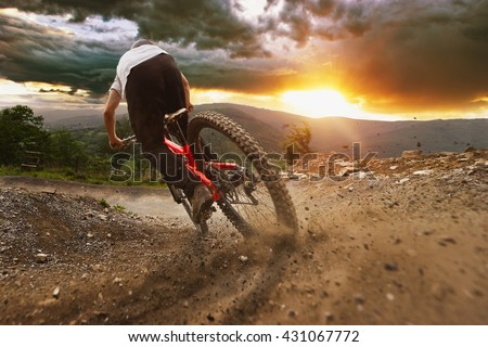 Man on mountain bike rides on the trail on a stormy sunset. - stock photo