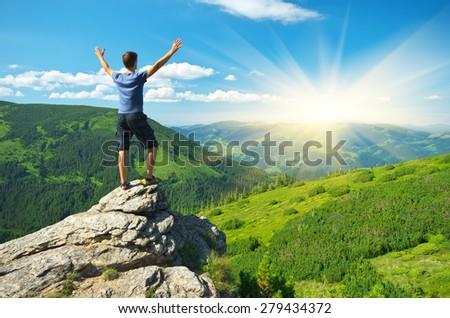 Man on peak of mountain. Emotional scene. - stock photo