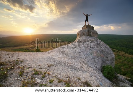 Man on peak of mountain. Nature and conceptual composition. - stock photo
