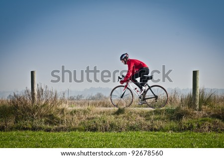 Man on road bike riding down open country road.