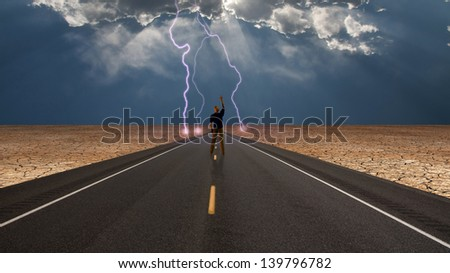 Man on road confronts storm - stock photo