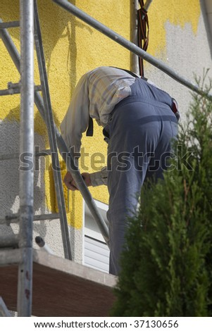 man on scaffold painting house with roller