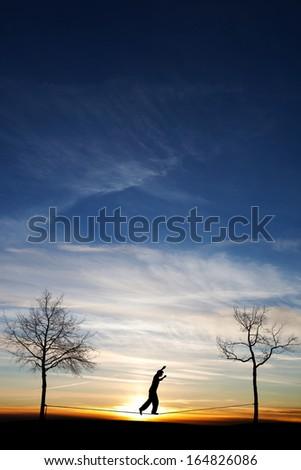 man on slackline  - stock photo