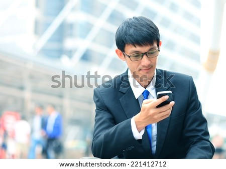 Man on smart phone - young business man. Casual urban professional businessman using smartphone smiling happy outside office building. Handsome man wearing suit outdoors.  - stock photo