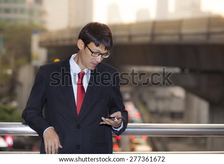 Man on smart phone - young business man. Casual urban professional businessman using smartphone smiling happy outside office building. Handsome man wearing suit outdoors.
