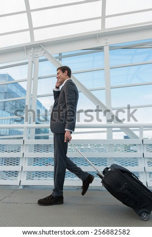 Man on smart phone - young business man in airport. Casual urban professional businessman using smartphone smiling happy inside office building or airport. Handsome man wearing suit jacket indoors. - stock photo
