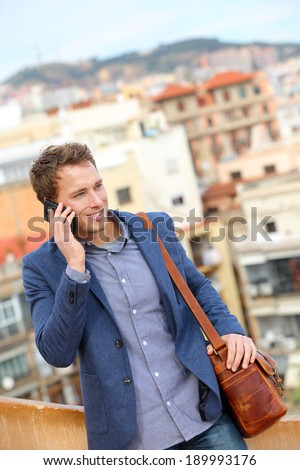 Man on smart phone - young business man talking on smartphone. Casual urban professional businessman using mobile cell phone smiling happy walking. Handsome man wearing suit jacket in Barcelona, Spain - stock photo