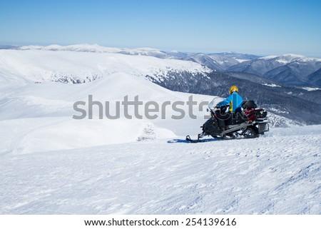 Man on snowmobile in winter mountain - stock photo