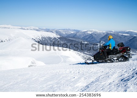 Man on snowmobile in winter mountain. - stock photo