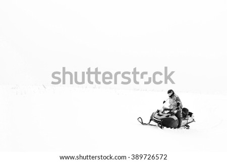 Man on snowmobile. Winter sports and entertainment. Black and white.