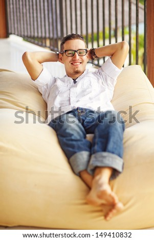 man on soft armchair in interior at home