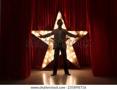 Man on stage with star on background - stock photo